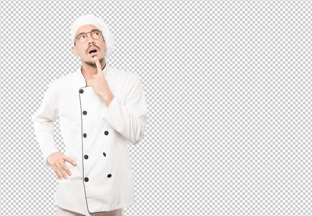 Удивленный молодой шеф-повар делает жест сомнения