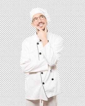 Счастливый молодой шеф-повар делает жест сомнения
