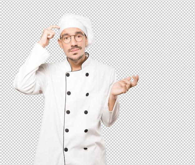 Обеспокоенный молодой повар делает жест растерянности