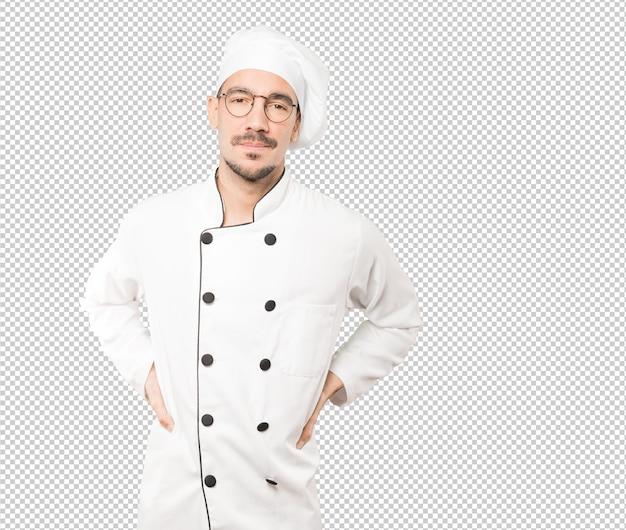 Усталый молодой шеф-повар позирует на фоне