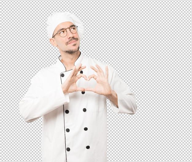 Счастливый молодой шеф-повар делает жест любви своими руками