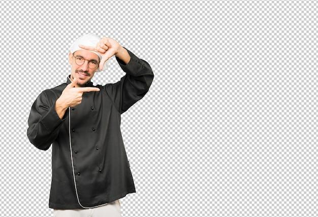 手で写真を撮るジェスチャーを作るフレンドリーな若いシェフ