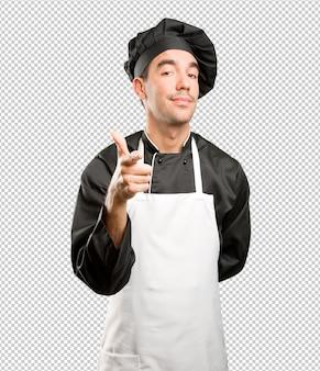 Уверенный молодой шеф-повар, указывающий
