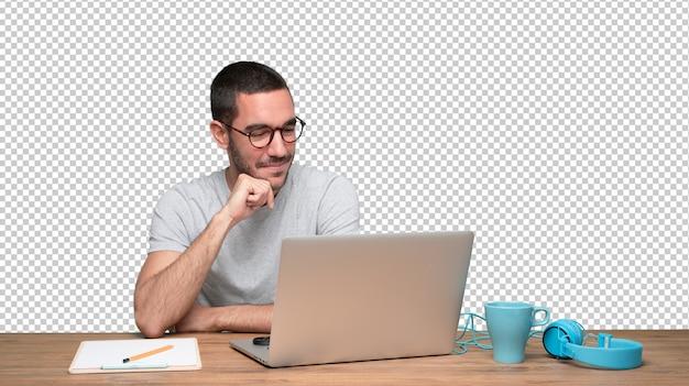 満足している若い男が机に座っている