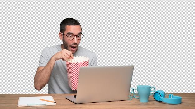 Удивленный молодой человек смотрит фильм на своем ноутбуке и есть попкорн