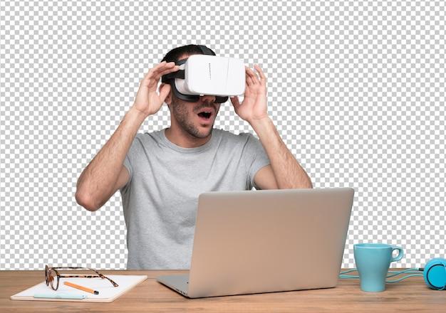 Удивленный молодой человек, сидящий за своим столом и используя очки виртуальной реальности