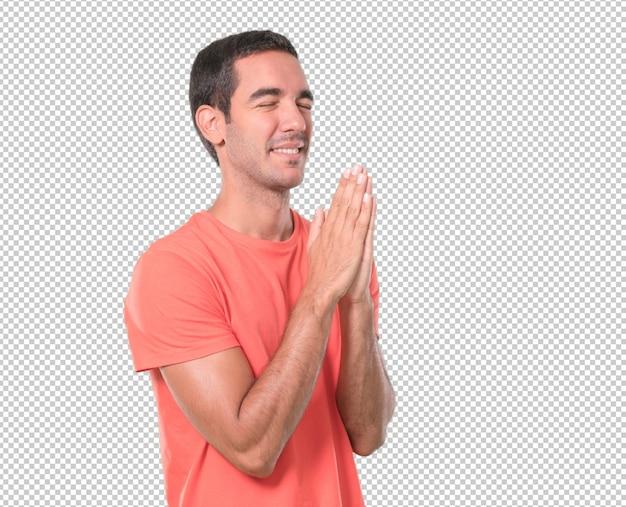 希望の若い男が祈っている