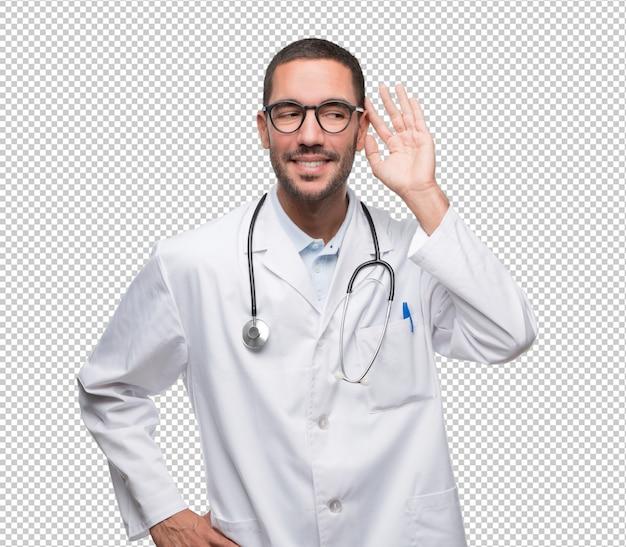 彼の手で耳を傾けようとするジェスチャーで幸せな若い医者