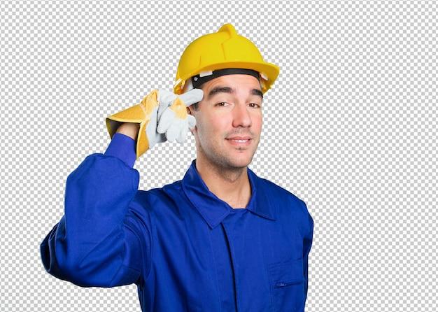 白い背景に集中のジェスチャーを持つ若い労働者