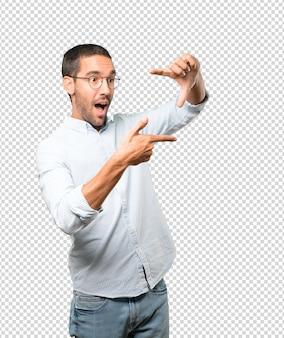 Удивленный молодой человек делает жест фотографирования руками