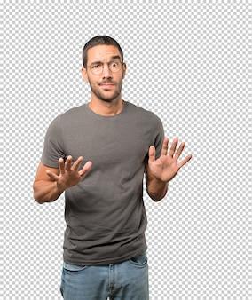 Сомнительный молодой человек делает жест спокойствия