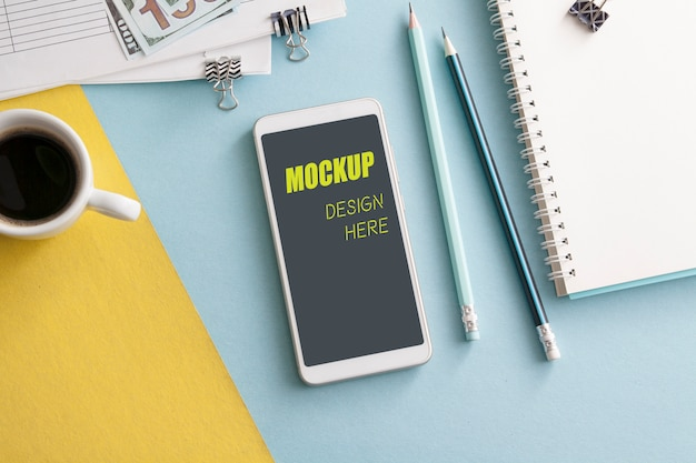 色付きのデスクトップの背景にノートブック、鉛筆、コーヒーを備えたモックアップのスマートフォン