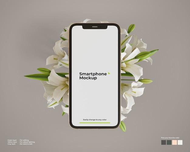 花の上のスマートフォンのモックアップ
