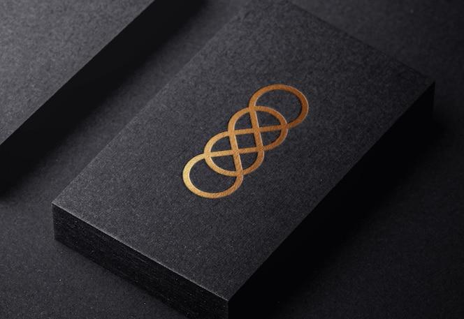 Роскошный золотой логотип макет на тисненой визитной карточке