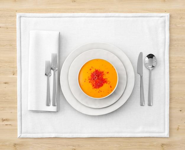 Суп на тарелке с сервировкой на деревянном столе