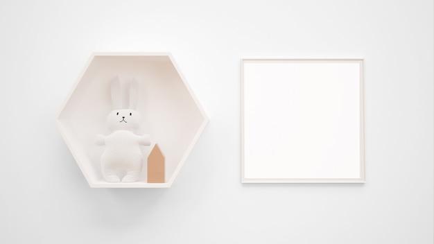 バニーのおもちゃの横の壁に掛かっている空白のフォトフレームモックアップ