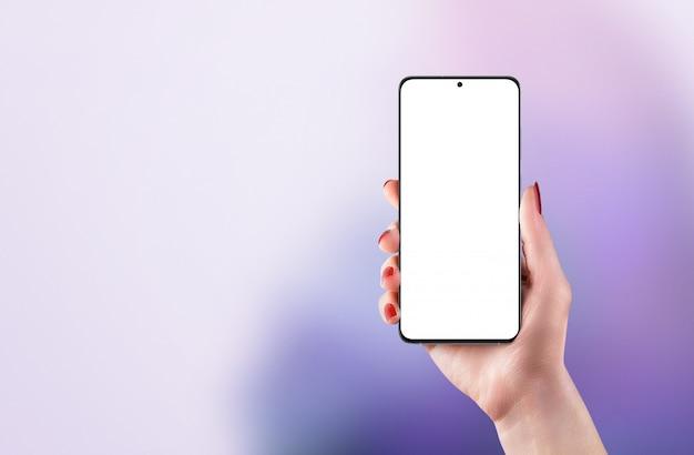 女性の手で電話のモックアップ。ディスプレイにカメラが組み込まれた最新の携帯電話。