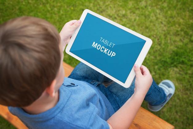 少年はモックアップの分離の白い画面でタブレットを使用します。