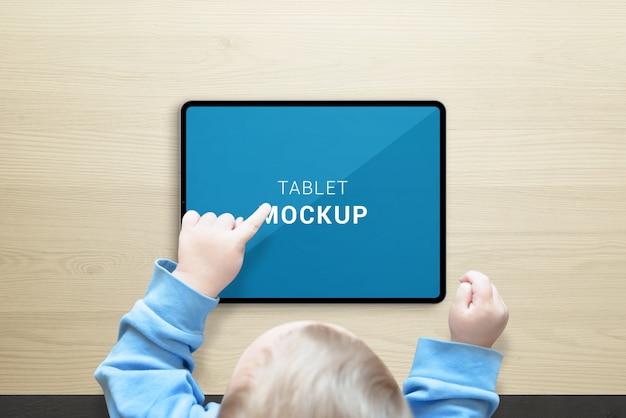 子供はタブレットのモックアップを使用します。トップビューシーン。水平姿勢のタブレット