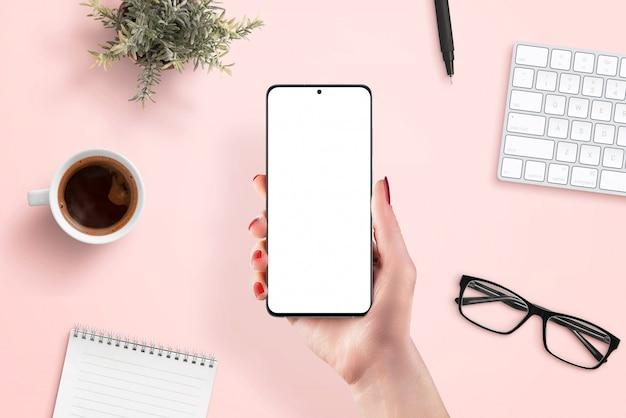 女性の手で電話のモックアップ。アプリプロモーションのクリーンシーン。トップビュー、フラットレイアウト。コーヒー、キーボード、植物、メガネ、パッド、ペンを背景にピンクのワークデスク