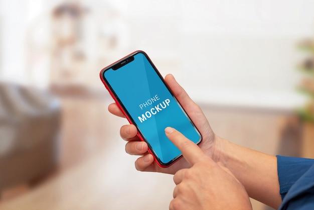 女性の手で水平位置に電話のモックアップ。紫色の抽象的な背景