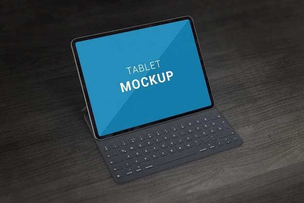 外部キーボードのモックアップを搭載したタブレット。木製のオフィスデスクの暗いシーン。閉じる。モックアップの分離画面。