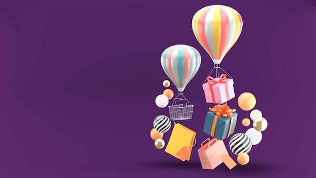 Воздушный шар, подарочная коробка и корзина в окружении разноцветных шариков на фиолетовом