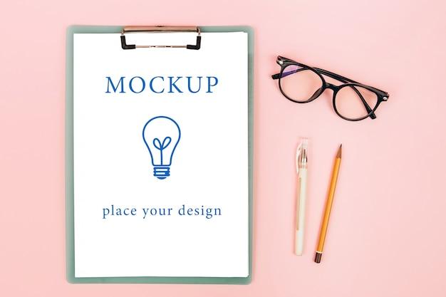 ピンクの背景、モックアップにメガネとノートの平面図