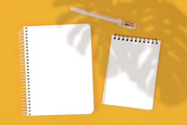 黄色の背景、モックアップ、シーンクリエーターのトップビューメモ帳