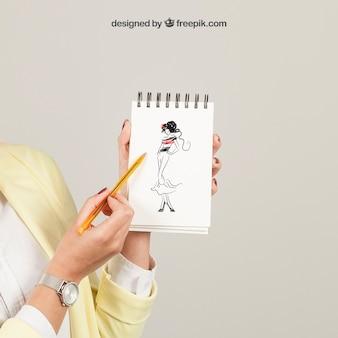Женщина показывает рисунок на блокнот