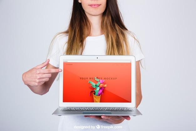 ラップトップを提示する女性のモックアップの概念