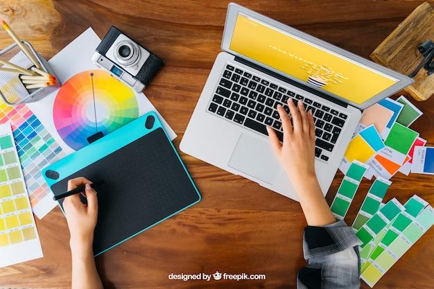 グラフィックタブレットとラップトップを備えたトップビューグラフィックデザイナーモックアップ