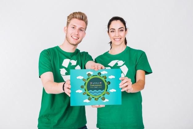 ボランティアカップル紙を持った世界環境デーモックアップ