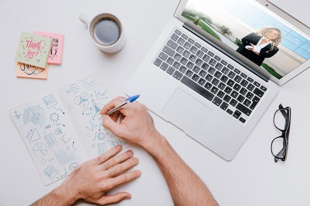 ノートパソコンの横に手を置いてワークスペースのコンセプト