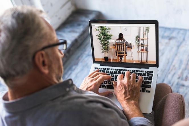 Пожилой человек, используя ноутбук