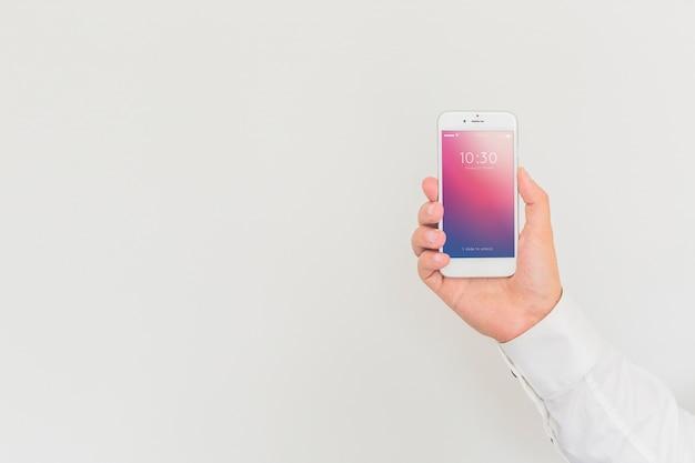 スマートフォンのモックアップを持っている男性の手