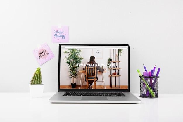 ノートパソコンと机の上にあるウェブサイトモックアップ