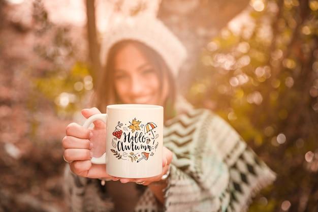 マグカップを持つ女性と秋のコンセプト