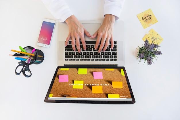 キーボードで入力する人とノートパソコンのモックアップ