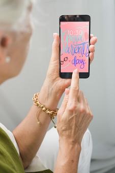 Старший женщина с помощью смартфона