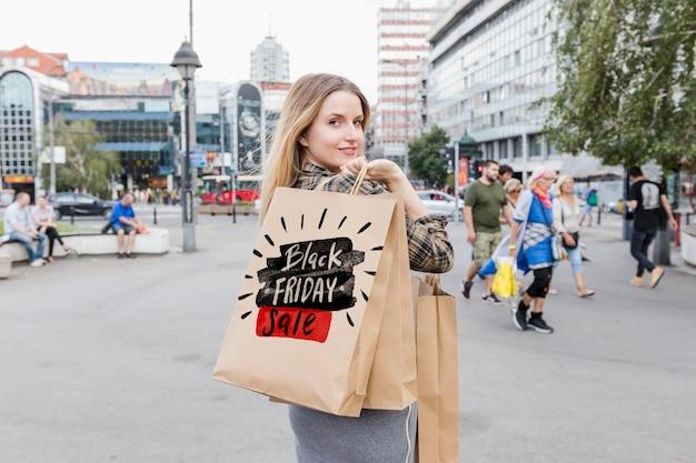 黒の金曜日の袋と都市の女性