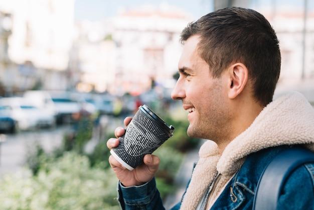 コーヒーカップのモックアップを持つ男の側面図