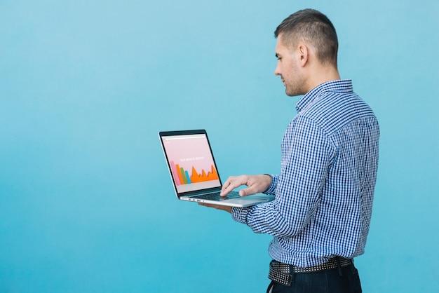ノートパソコンのモックアップを提示する男