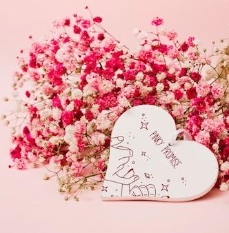 花の装飾とハートシェイプボックスのモックアップ