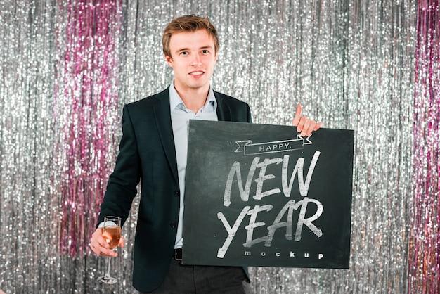 新年の黒板を持っている男