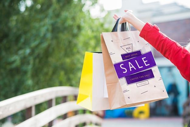 ショッピングバッグの模型を持つスタイリッシュな女性