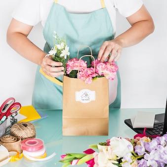 花と袋を準備する女性と園芸のコンセプト