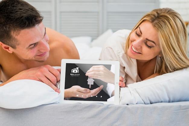 Пара в постели с макетом планшета для влюбленных