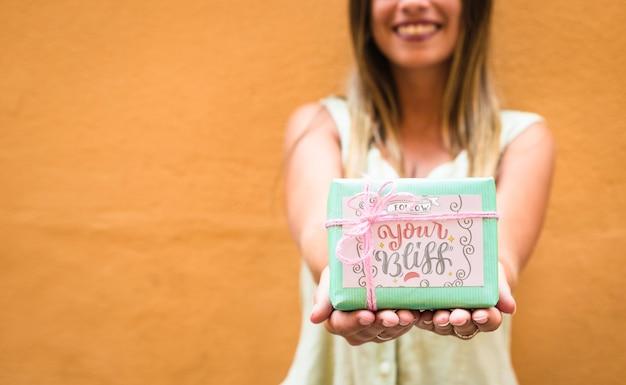 プレゼントボックスのモックアップを保持している女性