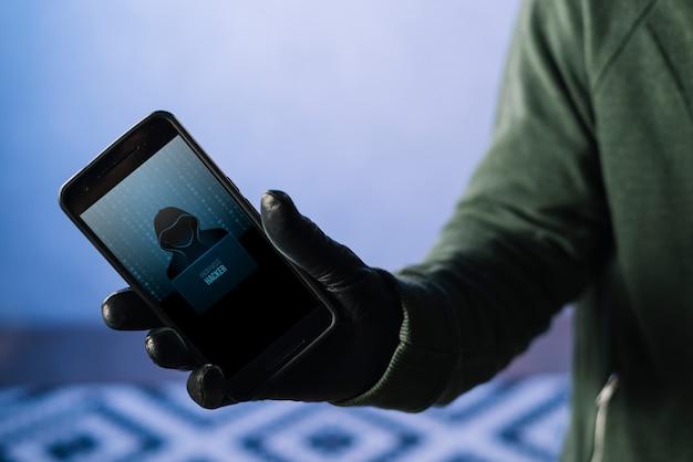 スマートフォンのモックアップを持つハッカー